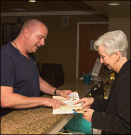 Dental Assistant Explaining Paperwork to Elderly Woman